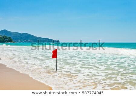 red flag on tropical beach stock photo © dutourdumonde