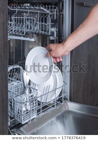 young man putting a dishwashing machine Stock photo © nito