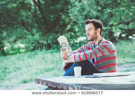 young man reading a book outdoors Stock photo © nito