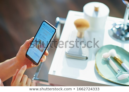 Woman holding modern mobile phone with online shopping applicati Stock photo © stevanovicigor