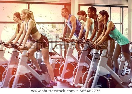 Fitness woman working out on spinning bicycle in gym Stock photo © deandrobot