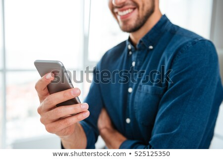 cropped photo of young man chatting by phone stock photo © deandrobot