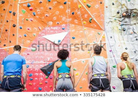 man looking at female athlete climbing wall in club stock photo © wavebreak_media