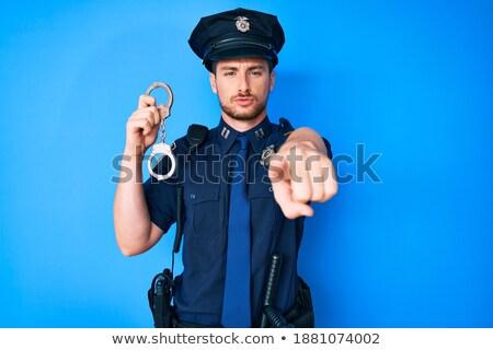 Młodych policjant kajdanki wskazując Zdjęcia stock © RAStudio