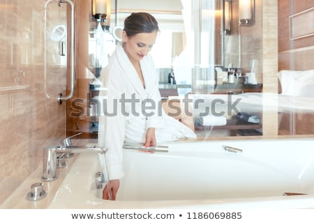 Woman in luxurious hotel bathroom letting water in the bathtub Stock photo © Kzenon