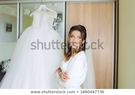 A beautiful young girl in a white robe is standing near the shelter and flips through a red folder w Stock photo © Traimak