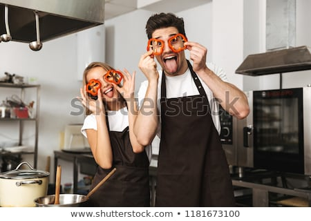 friends loving couple chefs on the kitchen having fun covering eyes with pasta stock photo © deandrobot