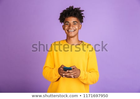Portrait of teenager boy with afro hairdo smiling and holding sm Stock photo © deandrobot