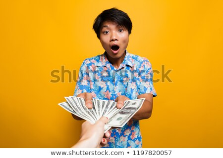 Astoinished asian man receiving money banknotes Stock photo © deandrobot