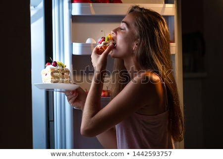 hungry woman eating food in kitchen stock photo © andreypopov