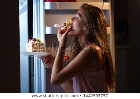 Faminto mulher alimentação comida cozinha sessão Foto stock © AndreyPopov