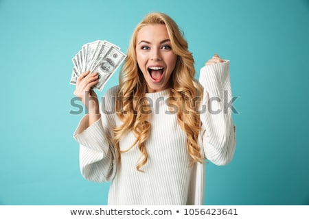 Beautiful woman isolated over blue background holding money. Stock photo © deandrobot