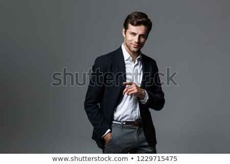 Portrait of adult handsome man in businesslike suit smiling to y Stock photo © deandrobot