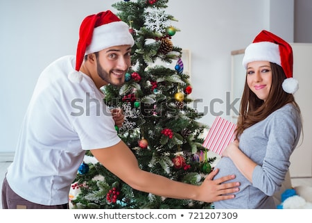 pregnant woman decorating christmas tree at home Stock photo © dolgachov