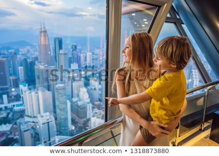 Mom and son are looking at Kuala lumpur cityscape. Panoramic view of Kuala Lumpur city skyline eveni Stock photo © galitskaya