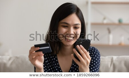 Happy young attractive woman with plastic card making online order Stock photo © pressmaster