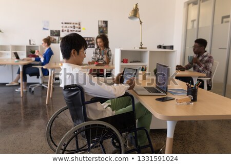 Side view of young Asian male executive using digital tablet in office with colleagues working in th Stock photo © wavebreak_media
