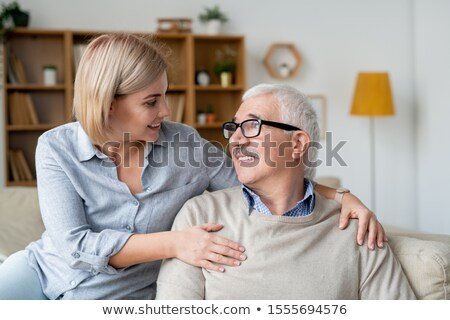 Restful senior man and his young daughter relaxing on couch and talking at home Stock photo © pressmaster