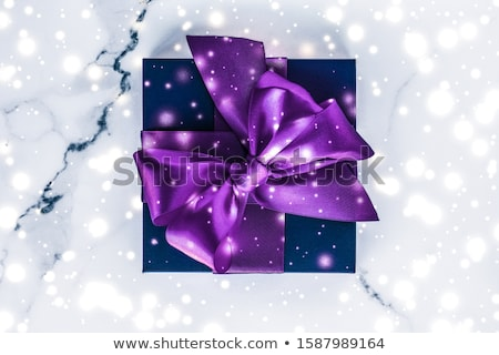 Winter holiday gift box with purple silk bow, snow glitter on ma Stock photo © Anneleven