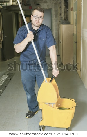 serviceman who cleaning the floor with his mop Stock photo © Lopolo