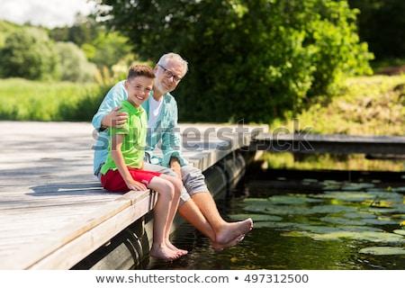 Dziadek wnuk posiedzenia rzeki rodziny pokolenie Zdjęcia stock © dolgachov