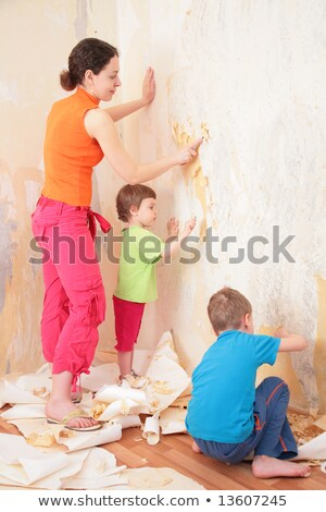 mother with children remove old wallpapers from wall Stock photo © Paha_L