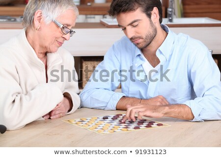 Senior woman playing checkers with a young man Stock photo © photography33