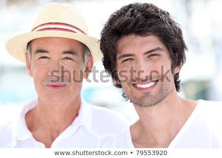 Stock photo: 65 years old man wearing a straw hat and a 25 years old man posing in a summer vacation atmosphere