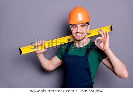 Grey-haired man holding spirit-level Stock photo © photography33