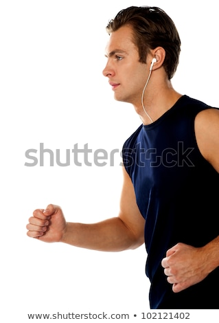 Fit athlete enjoying music in a jogging posture Stock photo © stockyimages