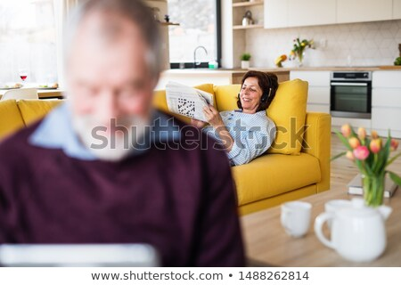 tender woman relaxing and listening to music from tablet stock photo © deandrobot