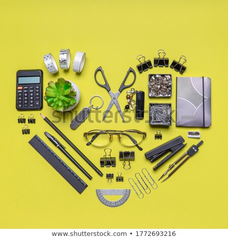 calculator notepad pen and green plant on grey background stock photo © punsayaporn