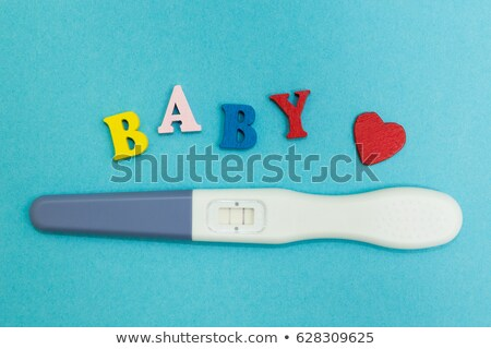 Woman holding positive pregnancy test with two blue stripes, clo Stock photo © Yatsenko