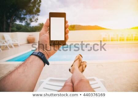 Adam cep telefonu yüzme havuzu gün batımı erkek Stok fotoğraf © stevanovicigor