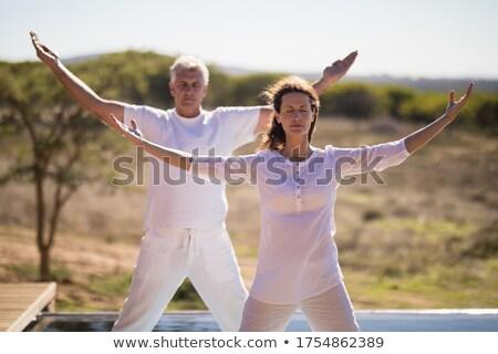 Couple practicing yoga on at poolside Stock photo © wavebreak_media