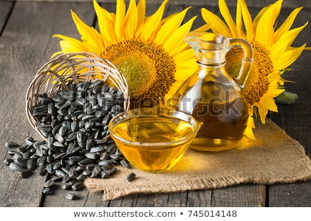 seeds oil and sunflower flower on wooden background stock photo © alinamd