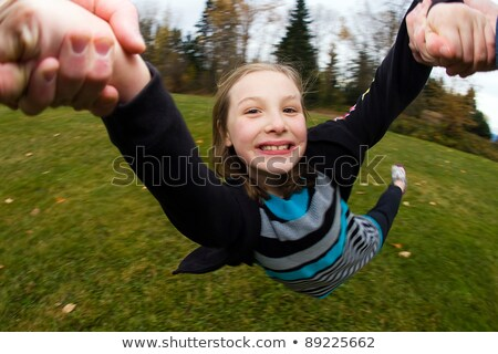 Parent swings daughter by her arms Stock photo © IS2