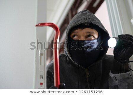 Thief With Flashlight And Crowbar Entering House Stock photo © AndreyPopov