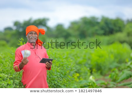 Surprised happy asian man receiving money banknotes Stock photo © deandrobot