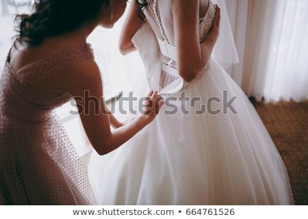 Stock photo: bridesmaids help to wear a wedding dress