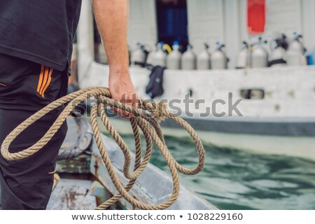 a man throws a rope to moor on a diver ship stock photo © galitskaya