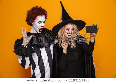Happy witch and clown making selfie on smartphone isolated Stock photo © deandrobot