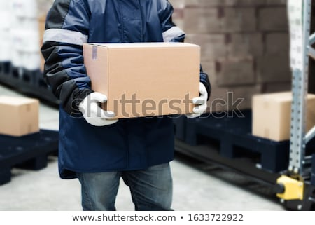 worker carrying loader with goods at warehouse Stock photo © dolgachov