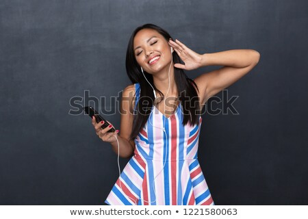 Image of delighted asian woman 30s wearing earphones listening t Stock photo © deandrobot
