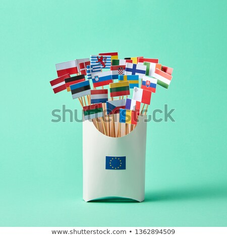 Different paper flags in a cardboard box with an EU sign and flag of Britain aside on green backgrou Stock photo © artjazz