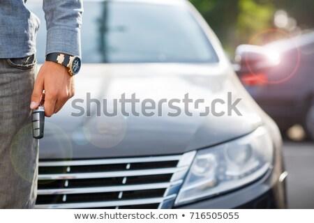 Hand  Holding key in front of cars Stock photo © wavebreak_media