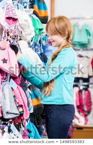 Girl looking at woolly hat in the shop Stock photo © Kzenon