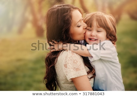 happy loving young mother kisses her toddler son on the walk stock photo © galitskaya