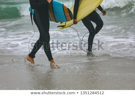 Low section of younf multi-ethnic male friends walking on beach while holding surfboards Stock photo © wavebreak_media