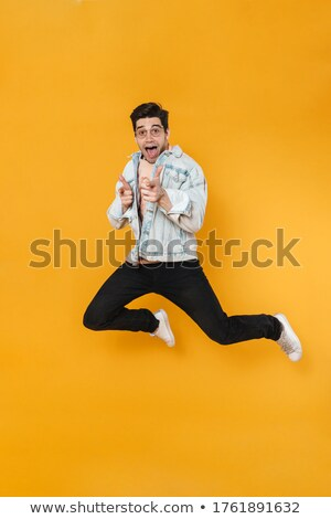 Photo of young delighted guys jumping and pointing fingers at camera Stock photo © deandrobot